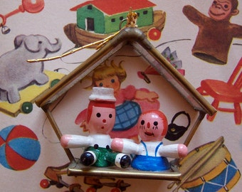 tiny wooden dolls under glass ornament