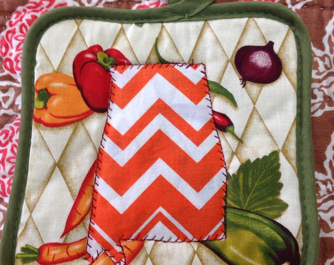 Pot holder with the state of Alabama in an orange and white cheveron pattern sewn on front.