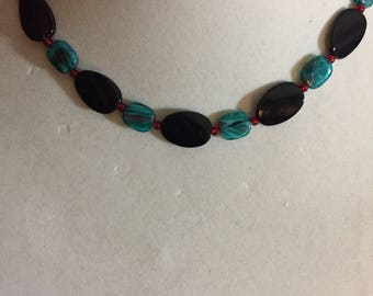 Black oval beads, aqua swirl beads and red seed beads necklace