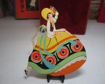 Gorgeous unused 1920's-30's art deco die cut Gibson bridge tally pretty lady wearing colorful dress w/deco designs matching hat , pantaloons