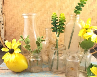 old glass bottles, seven various sized bottles, old and distressed vintage and antique bottles with greenery and black eyed susans, junk