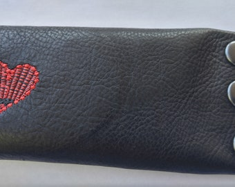 Black leather armband with red heart.