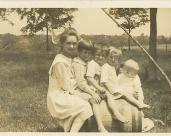 vintage photo 1918 Children Sit on an Oak Barrel All lined up with Hidden Mom holds Baby