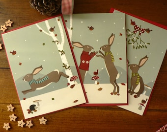 Set of 3 Christmas postcards featuring Christmas rabbits in the snow with red envelopes