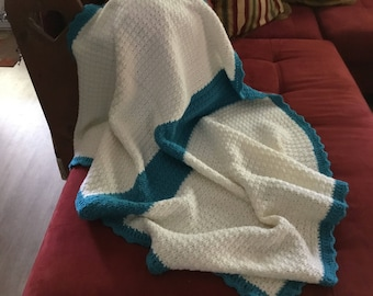 Crochet baby afghan in off qhite with aqua borders. This afghan is 38x45 inches.