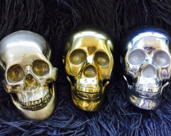 Vintage Lifesize Metal Halloween Skulls in Choice of Brass-Tone , Silver-Tone, or Antiqued Real Silver Finishes.