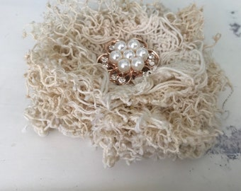"Handmade shabby  Doily flower. Aprox. 4"" diameter. Pearl and crystal rhinestone center in rose gold. Felt backing."