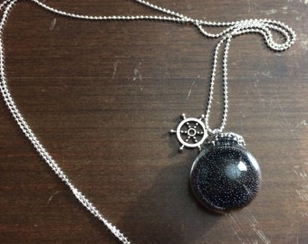 Necklace glass filled with black microbeads.