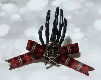 Plastic skeleton hand hair accessories with bow and skull detail.