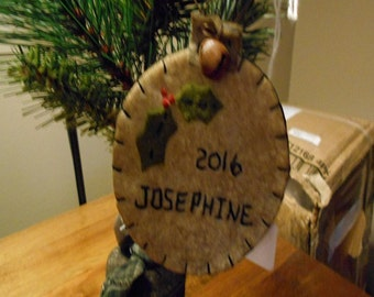Personalized ball ornament made of wool felt blend with holly, name and date stitched on its front.
