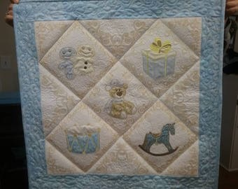 "Quilted baby wall hanging with appliqued and machine embroidered designs, size 26"" x 26"""