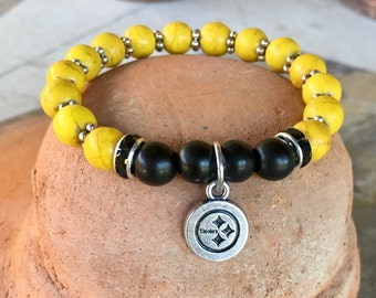Team spirit #yoga bracelet with black and yellow dyed turquoise beads, rhinestone spacers and #Steelers charm.