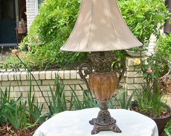 Old World Style Table Lamp With A Goldish Taupe Lamp Shade