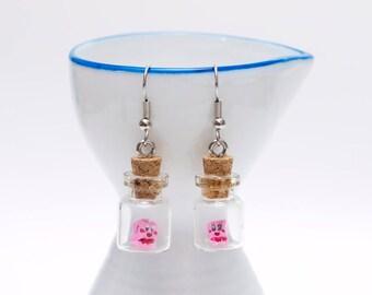 Origami Kirby earrings in tiny glass bottle