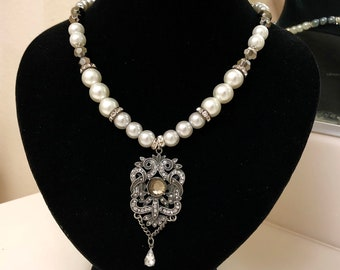 Short necklace with multiple shades of pearls and silver crystal beads with vintage pendant.