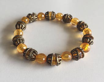 Bracelet perles transparentes orange avec intercalaires couleur bronze