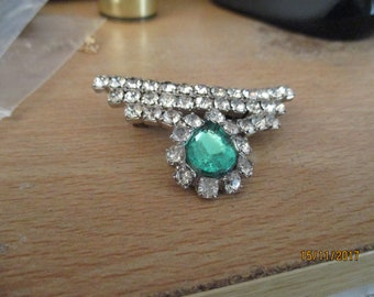 "vintage silvertone brooch with sparkling clear stones and one large emerald green stone 2.25""wide x 1.25""high in good condition"