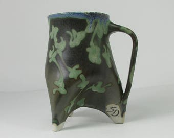 dark green tripod cup with minty flowers and a lime green interior