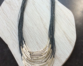 Multi strand necklace with textured noodle beads strung on fine waxed cord