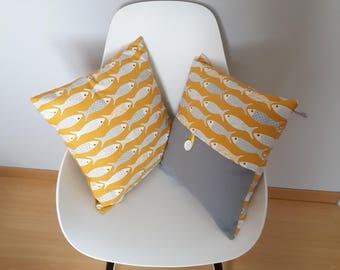 Light gray and white patterned small fish cushion on mustard yellow nautical decor