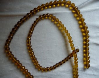 2 Strands of Glass Beads, Shades of Gold. Sold per 16 inch strands. The strands are 8mm and 10mm round beads.