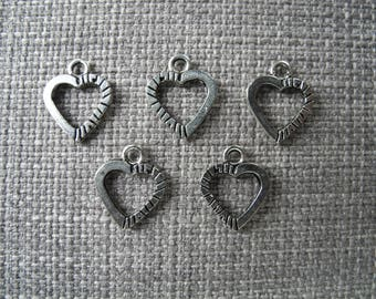 Hollowed and carved silver metal heart charm