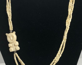 Carved bone multistrand bead necklace with carved bear
