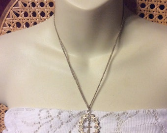 Rhinestone and pearl pendant necklace with brass cross.