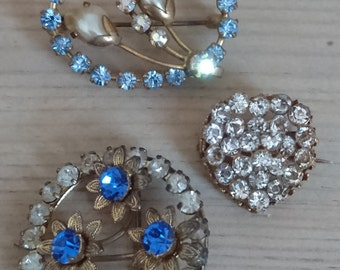 Three sparkly rhinestone brooches