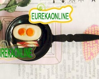 Miniature dolls hosue eggs and bacon in a frying pan