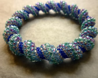 Spiral beadwork bangle in a range of mid blue shades