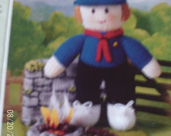 Handmade Knitted Girl Guide  Her Camp Fire On A Camping Trip stand With A Brick Background In Uniform
