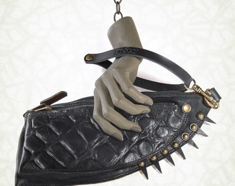 Virgola with spikes is a reinterpretation of the classic evening bag carried by hand, elegant but also bizarre. Leather. Handmade in Italy