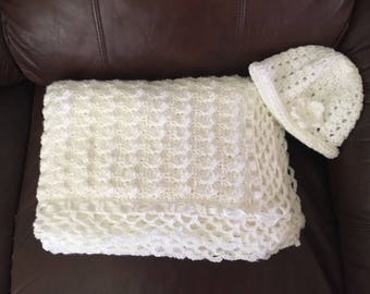 white baby blanket and hat