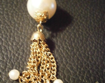 Gold tone necklace with faux pearl and chain dangles.