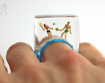 Resort de verano - verano playa figuras anillo con figuras jugando bádminton y de la arena en el anillo azul en resina para el estado de ánimo de vacaciones