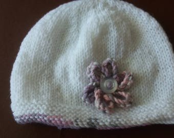 White hand knitted baby hat with lilac flower