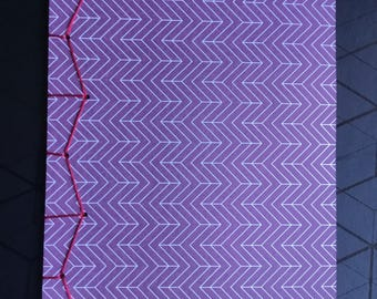 A5 stab bound journal with blank pages and a maroon zigzag stripped cover.
