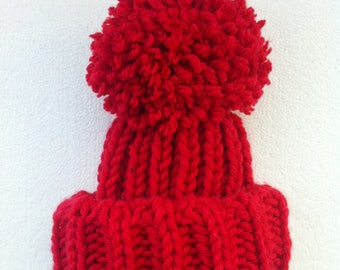 Babies red wooly Pom Pom hat . Chunky hand knit bobble hat.  Stretchy hat, cosy winter hat.  Newborn - toddler sizes.