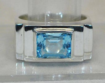 Big silver ring with blue topaz setting