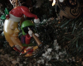 Marvin the martian sitting on a crescent moon ornament
