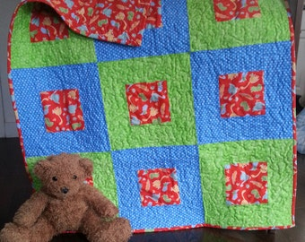Red, blue, and green dinosaur baby quilt