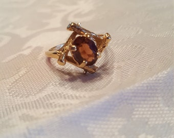 Unique gold tone ring with a brown rhinestone.