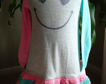 size 3T Big smile dress with one green and one pink long sleeve. Added hand crochet pink and green skirt. Hearts and smile.Leggings included
