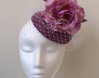 Stunning purple fascinator with 3 purple flowers with white netting.
