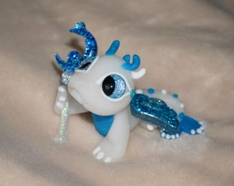 Polymer clay white fairy dragon with blue and silver glittery wings and wand