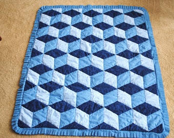 Crib quilt in tumble-block pattern for babies.