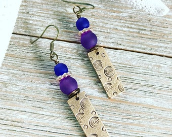 Hand stamped bronze tags wire wrapped with cobalt blue and purple frosted glass beads. Vintage bronze ear wires.
