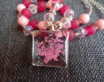 Pink flower pendant on a pink and gold beaded necklace