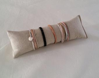 Display bracelet display jewelry in linen look beige fabric.